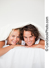 Portrait of a smiling couple under a duvet in their bedroom