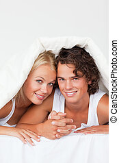 Portrait of a young couple under a duvet in a duvet