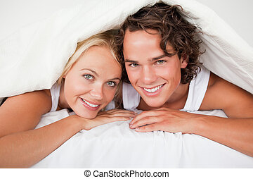 Couple under a duvet in a bed