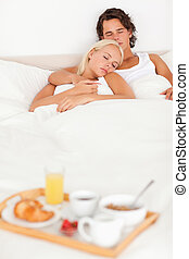 Couple sleeping with the breakfast served on a tray