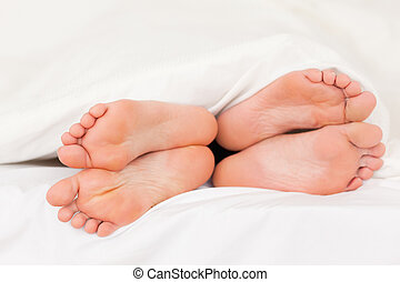 Two pair of feet in a bed
