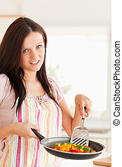 Woman frying vegetables in frying pan - A woman in the...