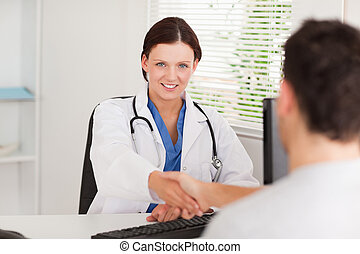 Female doctor hand shaking with patient - A female doctor is...