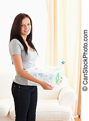 Woman holding filled recycling bin