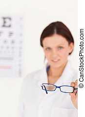 Blurred optician offering glasses