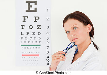 Female optician with eye test in office