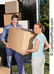 Happy Couple Moving - Smiling couple moving boxes at their...