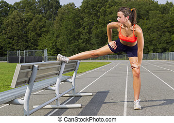 Young Athlete - An athletic teenager stretching before...