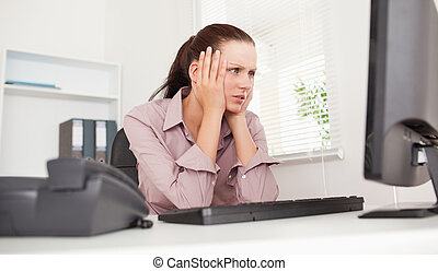 Stressed businesswoman looking to screen - A stressed...