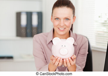 Businesswoman holding a piggy bank in office