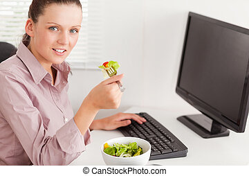 Businesswoman in office eating salad - A businesswoman...