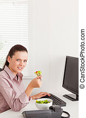 Businesswoman eats salad in her office - A businesswoman...