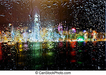 Drops of water on glass - Background of Night city through...