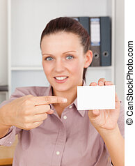 Red-haired business woman pointing at a card