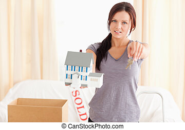 Young woman holding model house and keys in a living room