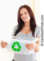 Gorgeous woman holding a recycling box in a living room