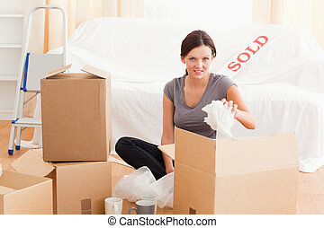 Charming woman packing her property in her former house