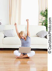 Portrait of a cheerful woman with a laptop while sitting on the floor in her living room