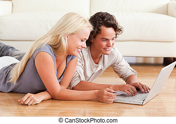 Young couple shopping online while lying on the floor