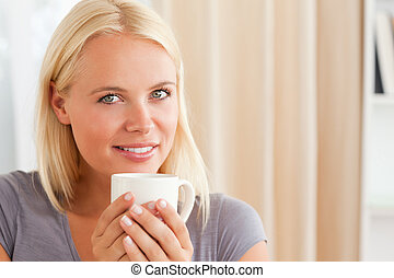 Calm woman sitting on a couch with a cup of tea in her livng...