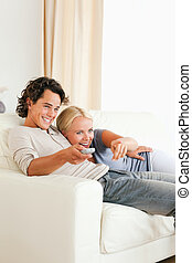 Portrait of a laughing couple cuddling while watching TV in...