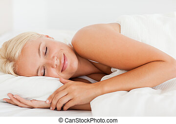 Smiling woman sleeping in her bedroom