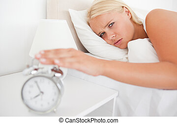 Tired woman awaken by an alarmclock in her bedroom
