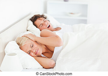 Annoyed woman awaken by her boyfriends snoring in their...