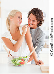 Portrait of a woman giving pepper to her fiance in their...