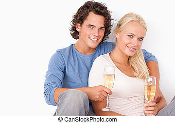 Couple with glasses of sparkling wine against a white...
