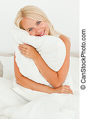 Woman holding a pillow sitting on her bed