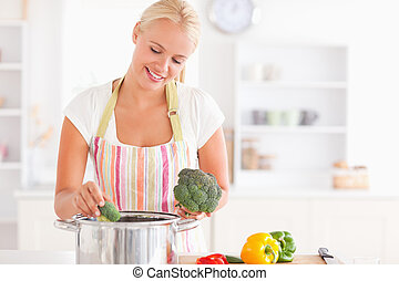 Woman putting cabbage on boiling water while wearing an...
