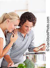 Portrait of a couple tasting a meal in their kitchen