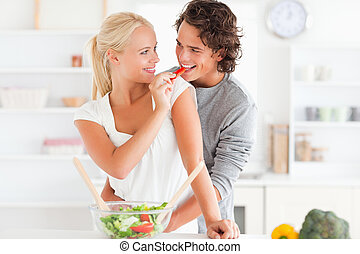Woman giving pepper to her fiance in their kitchen