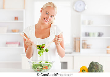 Cute woman mixing a salad in her kitchen