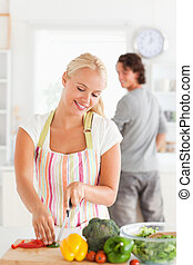 Portrait of a woman slicing pepper while her boyfriend is looking at her with the camera focus on her
