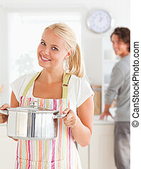 Portrait of a woman posing while her fiance is washing the dishes