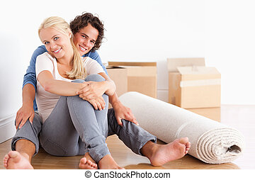 Happy couple sitting on the floor surrounded by boxes