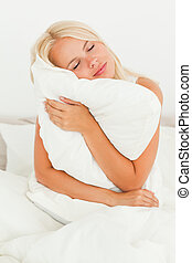 Blonde woman holding a pillow in her bedroom