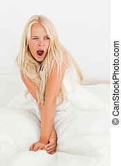 Portrait of a cute woman yawning sitting on her bed