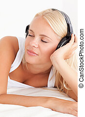 Portrait of a serene woman enjoying some music in her...