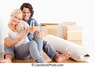 Happy couple toasting while sitting on the floor