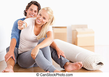 Woman sitting with her fiance giving keys with the camera...