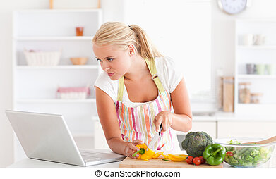 Woman using a laptop to cook in her kitchen