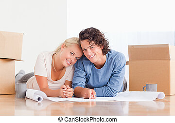 Couple organizing their future home surrounded by boxes