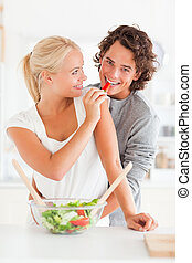 Portrait of a woman giving a slice of pepper to her fiance...