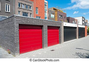 red garage doors belonging to a row newly built modern...