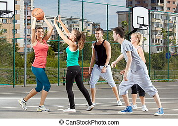 Leisure time - Young men and women playing basketball in a...