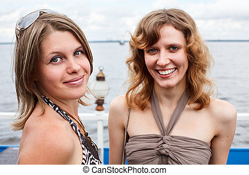 Two beautiful young women standing together and smiling