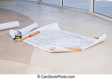 Blueprint on the floor with measuring tape and ruler